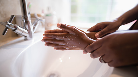 Cropped hands of mother assisting girl while washing hands at bathroom sink