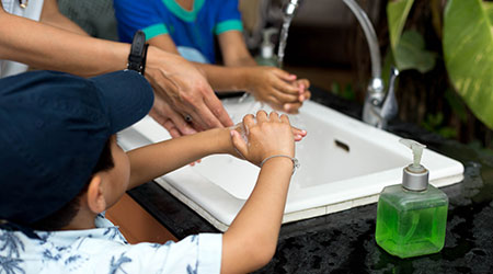 Selected focus littel boy washing hands in the sink outdoor with mum and sister in the park