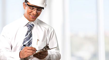 Man in a hard hat writing someone up while smiling