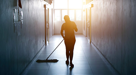 janitor dry mopping floor in hallway