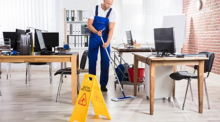 Male janitor cleaning empty office