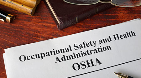 Occupational Safety and Health Administration (OSHA) worksheet, a pen and a book