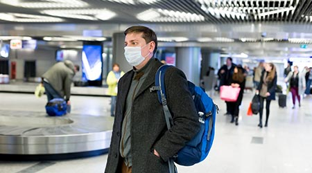 European man wearing a mask at the airport