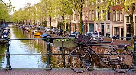 AMSTERDAM, NETHERLANDS - APRIL 14, 2019 :: Amsterdam canal Singel with typical dutch houses, Holland, Netherlands.