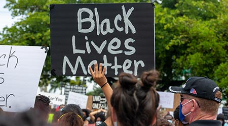 Black Lives Matter written in white on a black poster board held by a protester