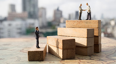 Miniature people, two of which are standing atop a staircase to shake hands, suggesting a hire or business deal
