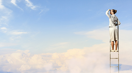 Businesswoman standing on a ladder above the clouds