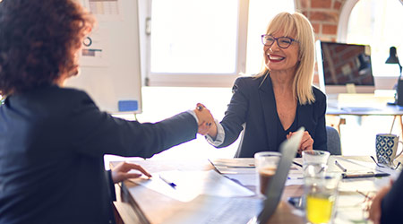 Businesswomen smiling and shaking hands