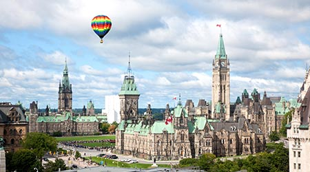 A hot air balloon flies over parliament hill in Canada