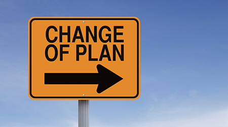 Change of plan written on black text on a yellow sign pointing to the right