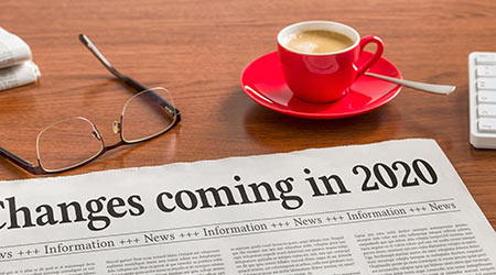 "A newspaper reading ""Changes Coming in 2020"" laid next to a pair of glasses and cup of coffee"