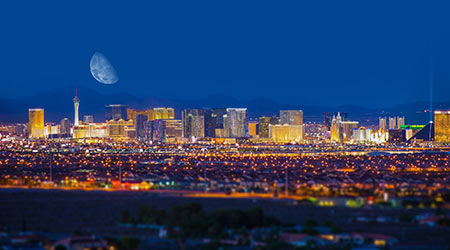 Panorama view of the Las Vegas Strip at night with moon appearing large in the sky