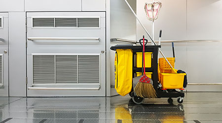 yellow janitor cart parked in a walk way