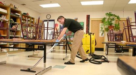 Man cleaning hard floor in school