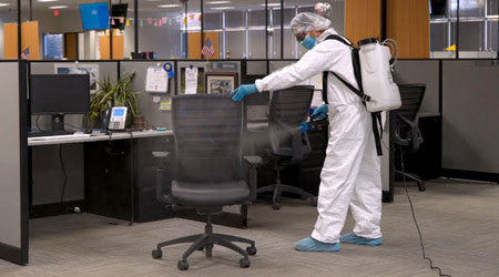 Janitor for a commercial cleaning company applies disinfectant fog to business