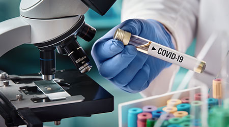 microbiologist with a tube of biological sample contaminated by Coronavirus with label Covid-19. doctor in the laboratory with a biological tube for analysis and sampling of Covid-19