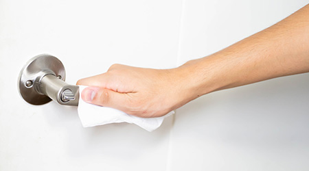 men use alcohol paper to hold Door knob to prevent infection and the covid 19 virus outbreak. Prevent Covid from touching the door.