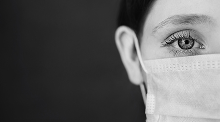 black and white photo of a woman wearing a protective mask
