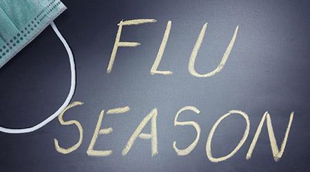 'Flu season' written on chalkboard next to a face mask