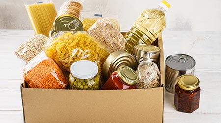 Various canned food, pasta and cereals in a cardboard box. Food donations or food delivery concept.  D