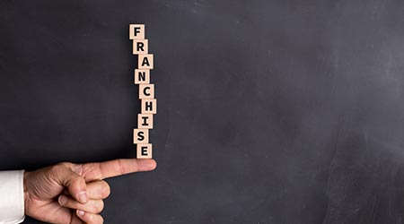 "building blocks spelling out the word ""franchise"" stacked up on a person's index finger"