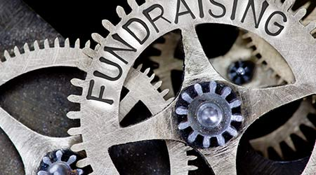 Macro photo of tooth wheel mechanism with FUNDRAISING concept letters