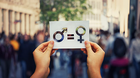 Gender equality concept as woman hands holding a white paper sheet with male and female symbol over a crowded city street background