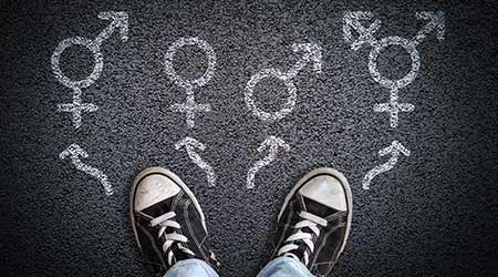 A person standing on asphalt road with gender symbols of male, female, bigender and transgender. Concept of choice or gender confusion or dysphoria.  R