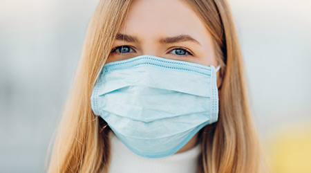 A young white woman wearing a face mask to combat COVID-19