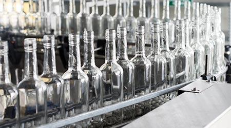 empty vodka bottles on conveyor belt