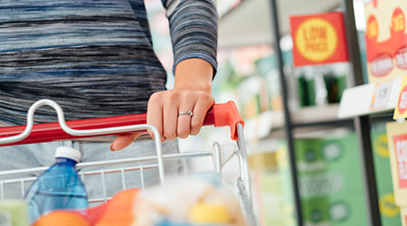 Woman doing grocery shopping at the supermarket and pushing a full shopping cart, hand detail close up, lifestyle concept  S