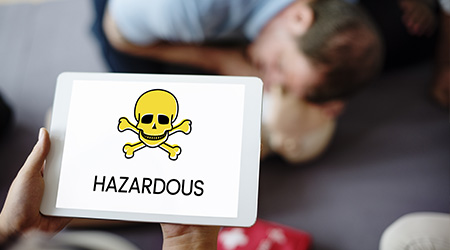 Smart pad with image of skull and crossbones on its screen as man curls over after chemical exposure