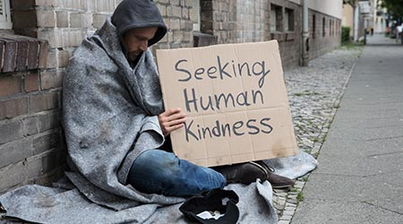 Homeless man holding up a depressing sign