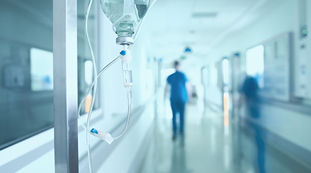 Silhouette of a a healthcare professional walking through a hospital corridor with an IV also shown in the forefront