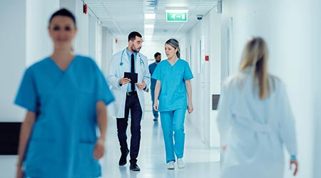 A doctor and a nurse walking side by side down a hospital hallway