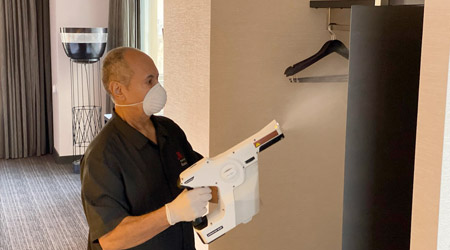 Hotel staff member using an electronic sprayer