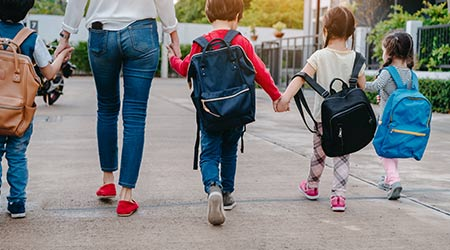 Mother walking hand by hand with several very young elementary school children wearing backpacks