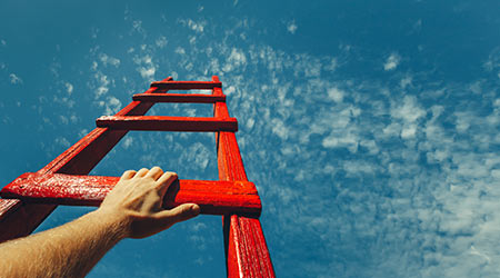 A person climbing a latter pointed at the sky. the sky is the limit