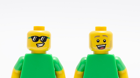 Two Lego minifigures - one wearing sunglass and one happy. Lego minifigures are manufactured by The Lego Group.