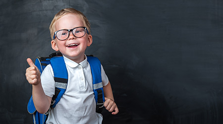 Happy smiling boy in glasses with thumb up is going to school for the first time. Child with school bag and book. Kid indoors of the class room with blackboard on a background. Back to school.  S