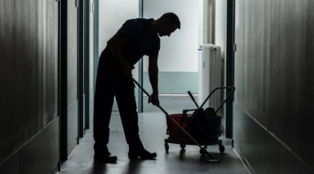 Silhouette of a male janitor moping a dark room