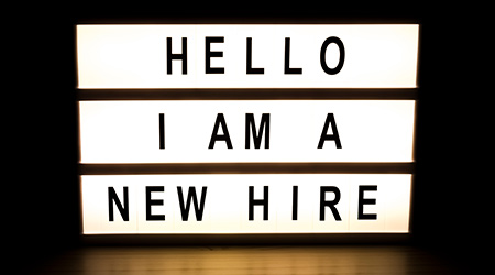 "light box sign reading ""hello I am a new hire"""