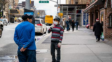 A man working at a nearby business wears gloves and a medical mask to protect against COVID-19 or Coronavirus in Washington Heights, New York City.