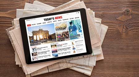 A tablet with the news showing sitting on top of newspapers