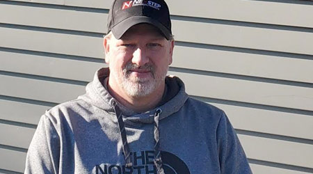 Middle aged man in a ball cap and North Face sweater