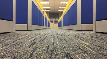 The carpet floor in an office filled with cubicles