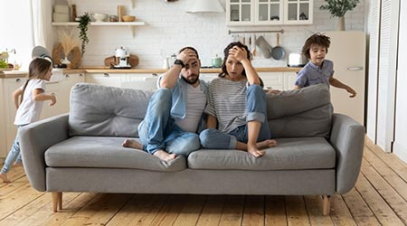 Tired mother and father sitting on couch feels annoyed  and exhausted while noisy little daughter and son shout and run around sofa where parents resting. Two hyperactive kids, need repose concept