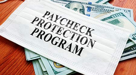PPP Paycheck Protection Program as SBA loan written on the mask and money