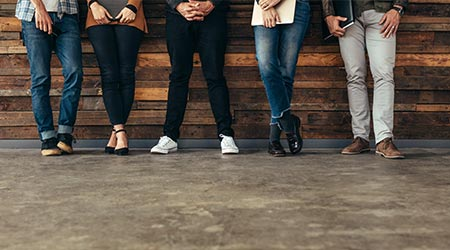 Group of people leaning against the wall before a job interview with folders in hands in the waiting room. Cropped shot of legs of people standing in row waiting for job interview.