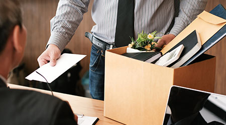 Man handing in his letter of resignation while carrying the belongings from his desk